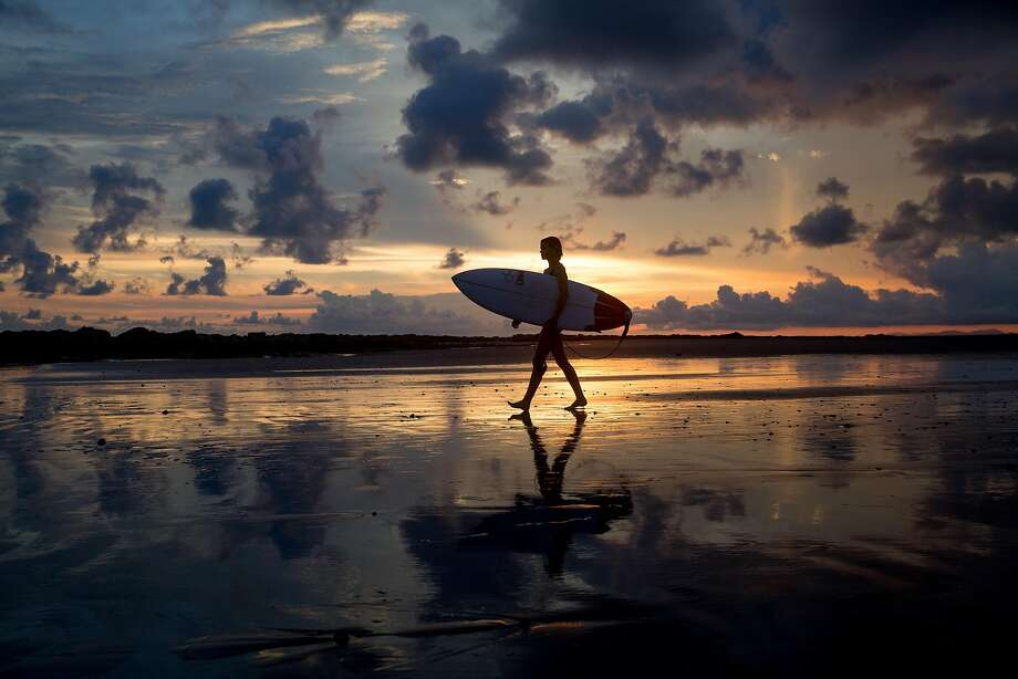 A surfer walks down a beach during sunset in Mal Pais, Costa Rica. For some Bay Area tech employees, unlimited paid vacation days are a reality. Photo: Gabe LHeureux, Getty Images