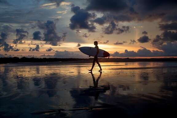 MAL PAIS, COSTA RICA - JUNE 13: A female surfer walks down beach during sunset on June 13, 2015 in Mal Pais, Costa Rica. (Photo by Gabe LHeureux/Getty Images)