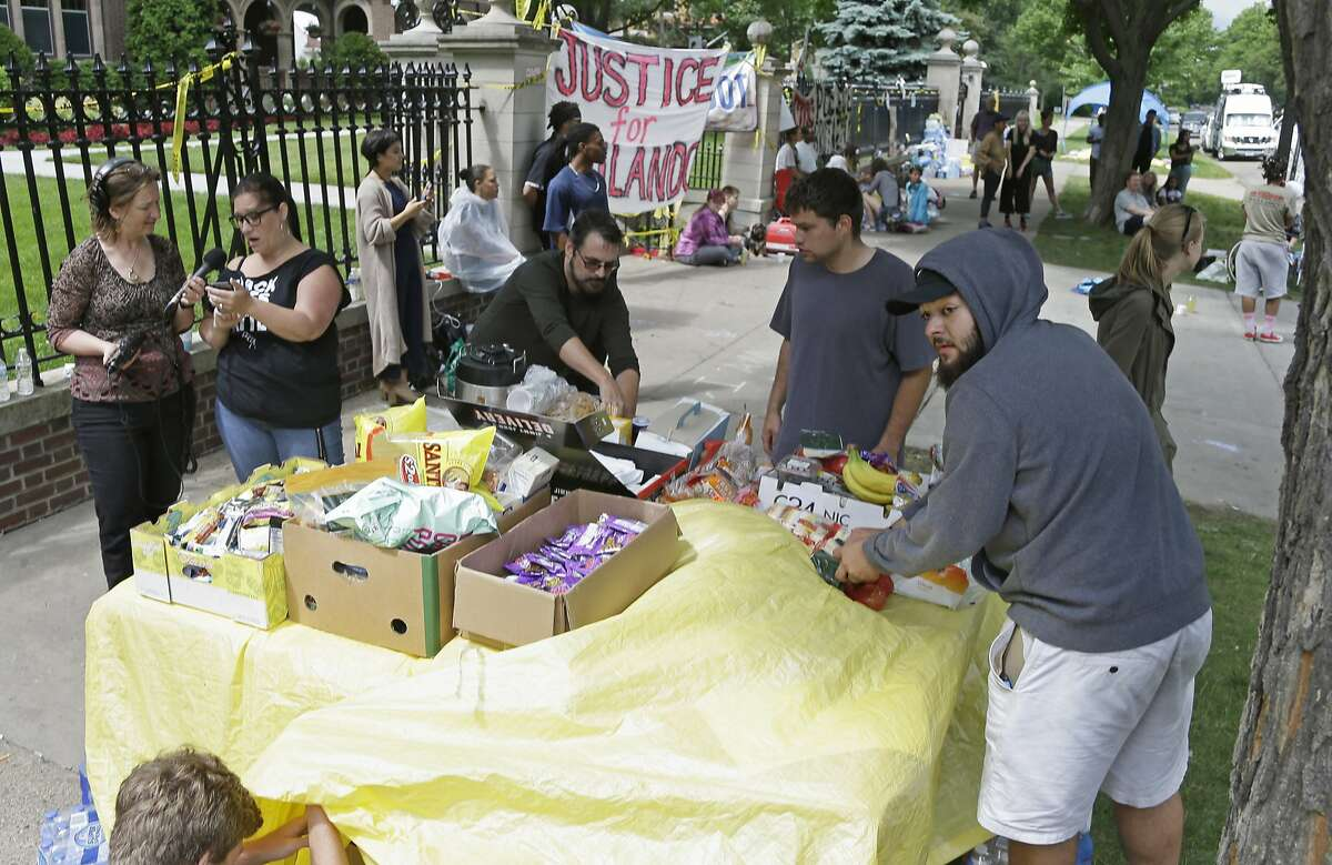 Demonstrators set up a food table outside the governor's residence Friday, July 8, 2016, in St. Paul, Minn. , where protests continue over the shooting death by police of Philando Castile after a traffic stop Wednesday, July 6, in Falcon Heights. (AP Photo/Jim Mone)
