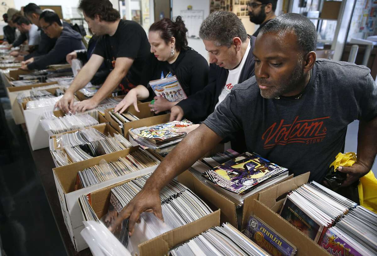 Fredrick Jackson (right) searches for valuable titles with Ian Morton (center) and Reyna Young (left) at a comic book sale by the Friends of the San Francisco Public Library in San Francisco, Calif. on Saturday, July 9, 2016.