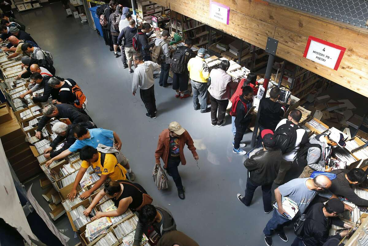 Dozens of comic book fans search through boxes of titles at a sale by the Friends of the San Francisco Public Library in San Francisco, Calif. on Saturday, July 9, 2016.