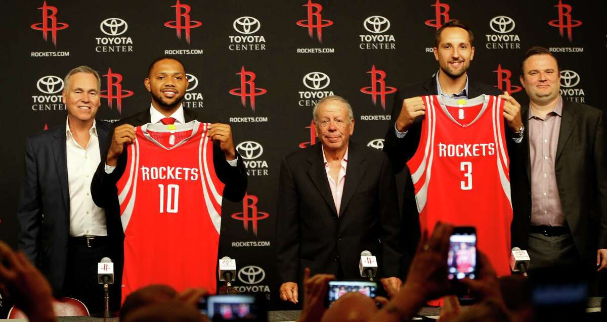"""Eric Gordon holds his jersey with """"10"""" and Ryan Anderson holds his with a """"3"""" as they take photos with coach Mike D'Antoni, owner Leslie Alexander, and GM Daryl Morey during a press conference at the Houston Rockets, Saturday, July 9, 2016, in Houston, as they introduced free-agent signees Ryan Anderson and Eric Gordon."""