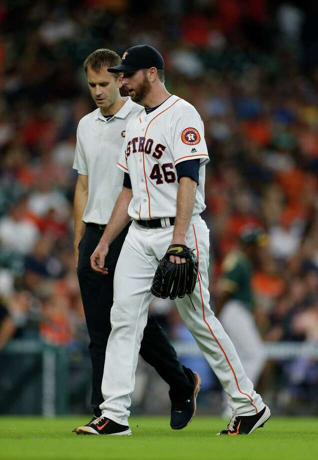 Houston Astros relief pitcher Scott Feldman leaves the game with trainer Jeremiah Randall in the ninth inning of an MLB baseball game at Minute Maid Park, Saturday, July 9, 2016, in Houston. Photo: Karen Warren, Houston Chronicle / © 2016 Houston Chronicle