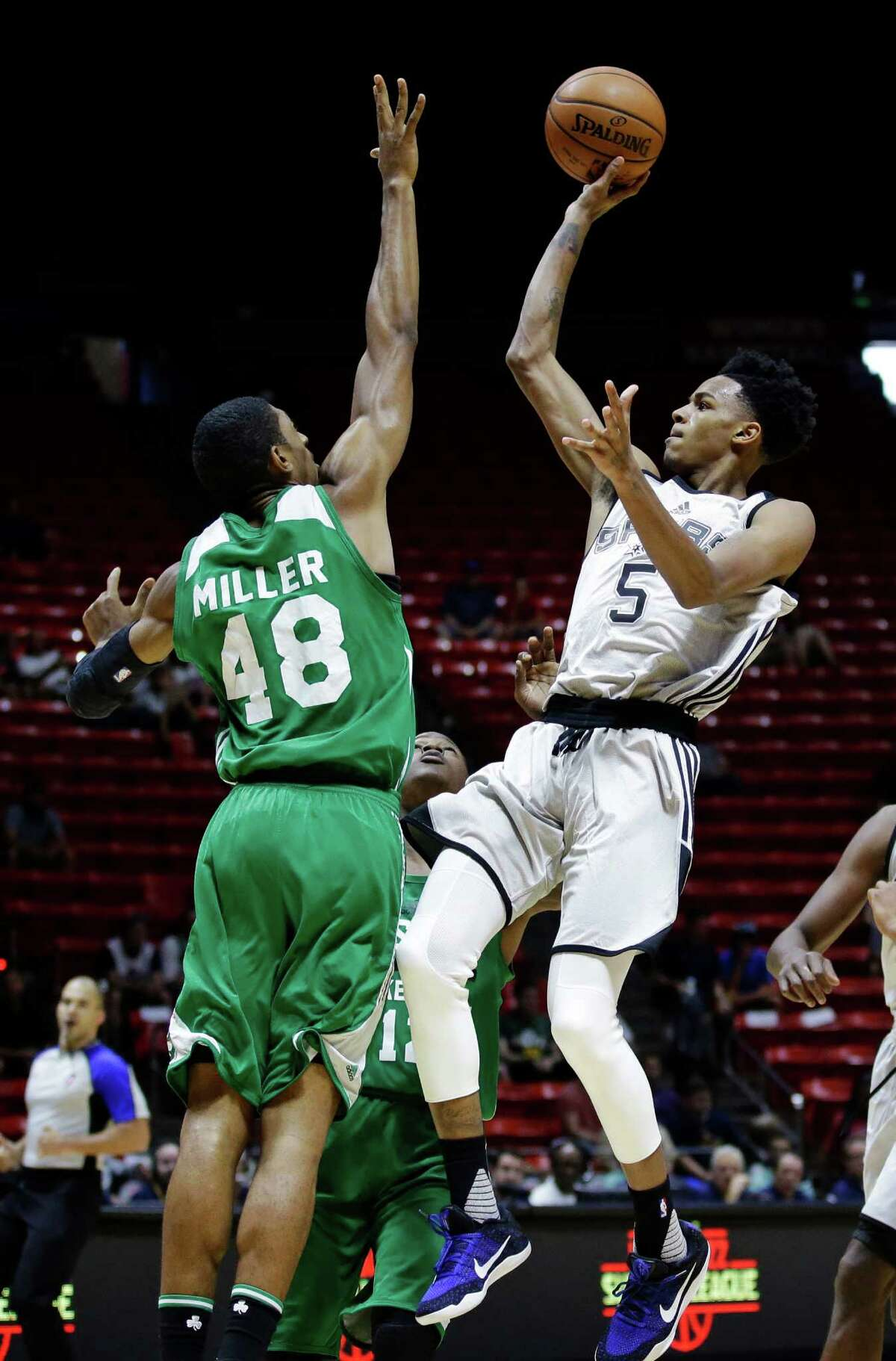 Spurs guard Dejounte Murray shoots as Boston Celtics forward Malcolm Miller defends during the first half of an NBA Summer League game on July 7, 2016, in Salt Lake City.