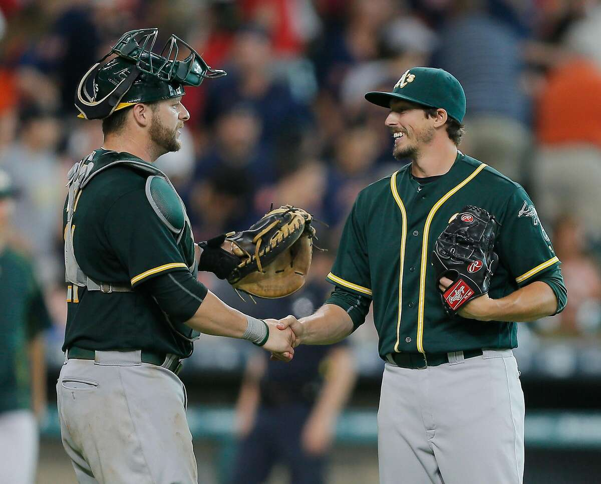 HOUSTON, TX - JULY 09: Ryan Dull #66 of the Oakland Athletics, right, shakes hands with catcher Stephen Vogt #21 of the Oakland Athletics after the final out against the Houston Astros at Minute Maid Park on July 9, 2016 in Houston, Texas. (Photo by Bob Levey/Getty Images)