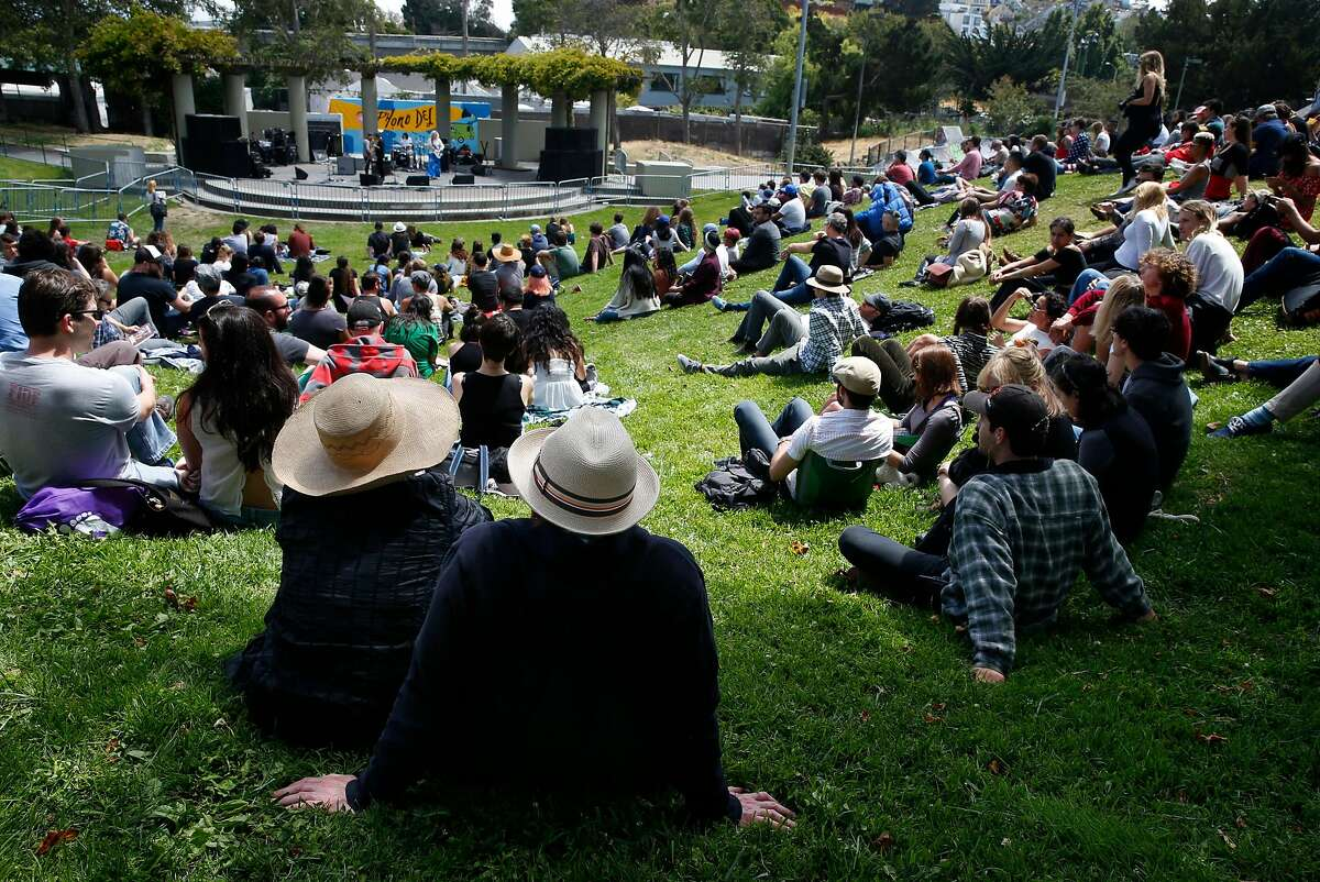 Kim Freeman (left) and Quinton Huckeby listen to a music set from The She's during the Phono del Sol music festival at Potrero del Sol Park in San Francisco, Calif. on Saturday, July 9, 2016.