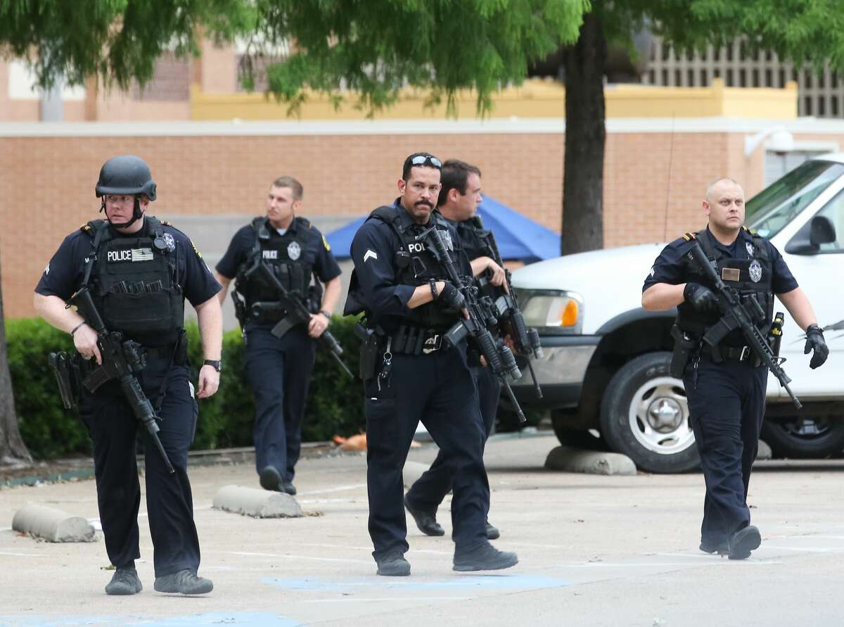 Police search the parking lot of the Dallas Police Department headquarters, Saturday, July 9, in Dallas. ( Jon Shapley / Houston Chronicle )