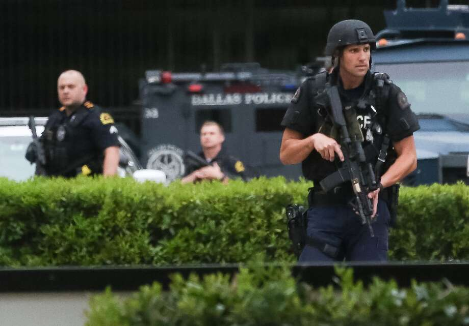 Police search the parking lot of the Dallas Police Department headquarters, Saturday, July 9, in Dallas. ( Jon Shapley / Houston Chronicle ) Photo: Jon Shppley ,  Houston Chronicle