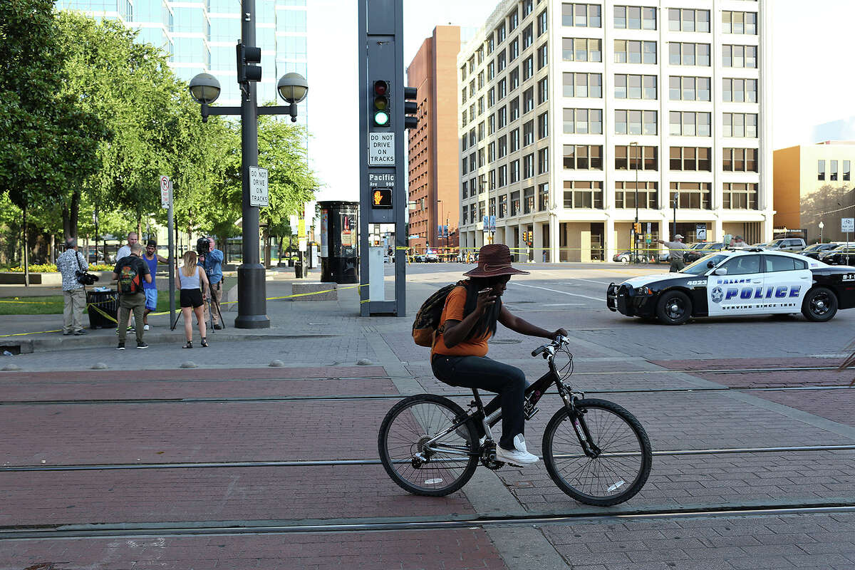 A cyclist passes the scene, still under investigation, next to El Centro College, right, where police officers were killed and inured on Thursday night in Dallas on Friday, July 8, 2016.
