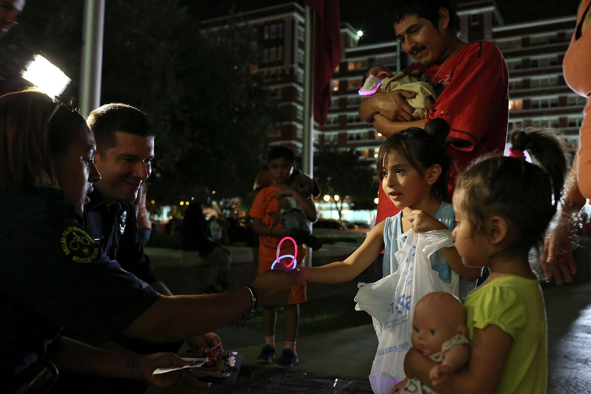 Aliyah Martinez, 5, and her sister, Amaris, 2, hand out cards, glow brackets and ring pops to Police Officers K. Pate, left, and M. Bono outside Dallas Police Department Headquarters on Friday, July 8, 2016. Watching is their father, Armani Martinez, holding Ava, four months.