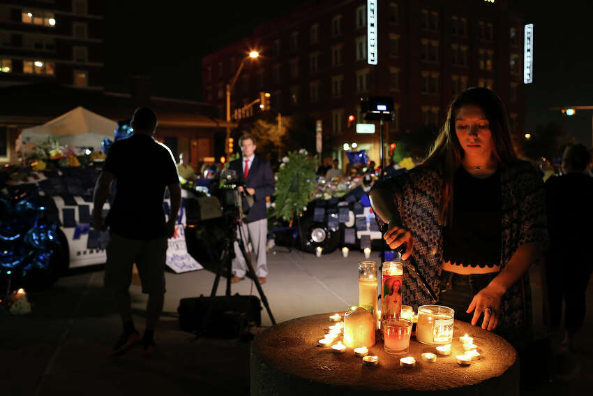 Shelby Garcia, 16, of Midlothian, lights candles at the memorial to the slain and injured officers outside Dallas Police Department Headquarters on Friday, July 8, 2016.