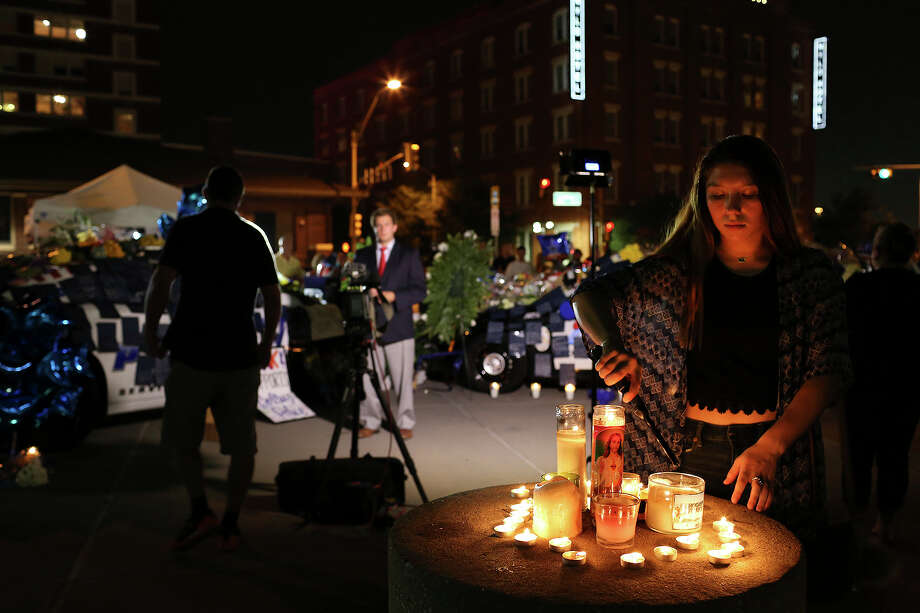 Shelby Garcia, 16, of Midlothian, lights candles at the memorial to the slain and injured officers outside Dallas Police Department Headquarters on Friday, July 8, 2016. Photo: Lisa Krantz / Lisa Krantz / SAN ANTONIO EXPRESS-NEWS
