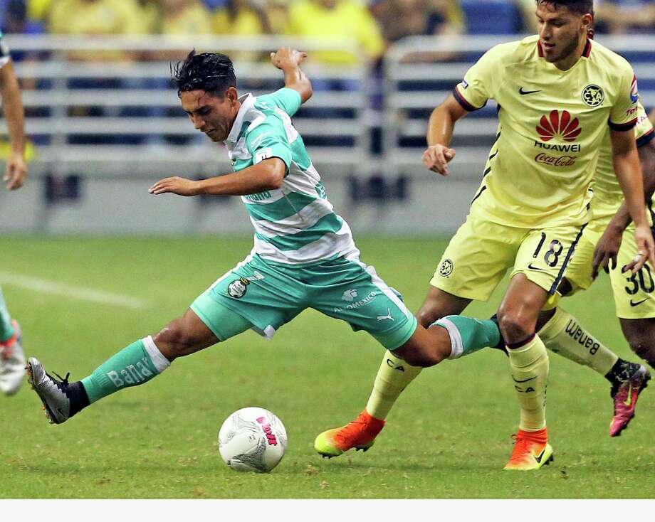 (7) from Club Santos Laguna stretches over the ball and then is tripped up by (18) from Club America during a Mexican League exhibition soccer match between Club America and Club Santos Laguna at the Alamodome on July 9, 2016. Photo: TOM REEL, STAFF / SAN ANTONIO EXPRESS-NEWS / 2016 SAN ANTONIO EXPRESS-NEWS