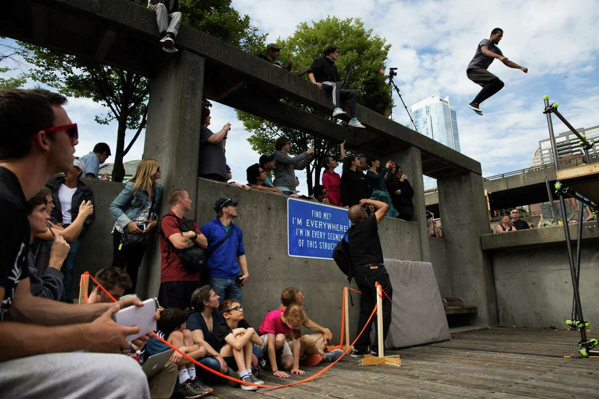Brian Prince leaps to a thin landing on a bar during the style portion of the Western Parkour Championships at Waterfront Park on Saturday, July 9, 2016.