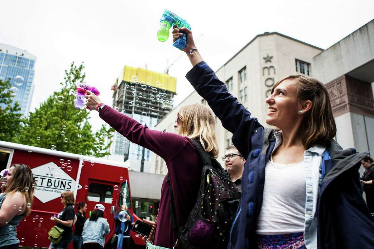 Flash mob participants use bubble guns during the International Bubble Flash Mob at Westlake Park in downtown Seattle on July 9, 2016.