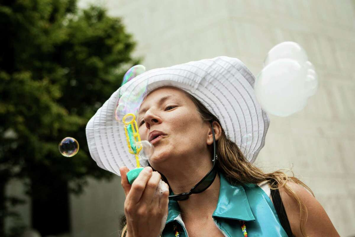 A woman blows vapor into bubbles during the International Bubble Flash Mob at Westlake Park in downtown Seattle on July 9, 2016. The flash mob lasted 30 minutes in both Seattle and London.