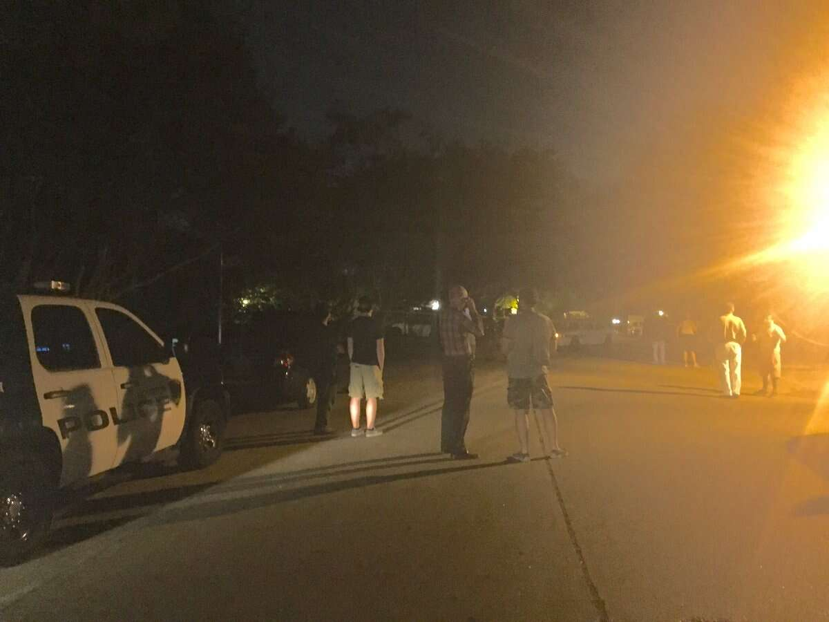 Neighbors wait in the street while SWAT team deals with holed up suspect, who neighbors call reputedly unstable