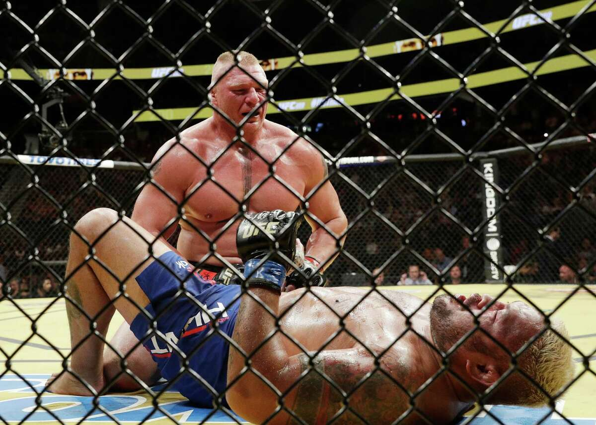 Brock Lesnar kneels over Mark Hunt during their heavyweight mixed martial arts bout at UFC 200, Saturday, July 9, 2016, in Las Vegas. (AP Photo/John Locher)