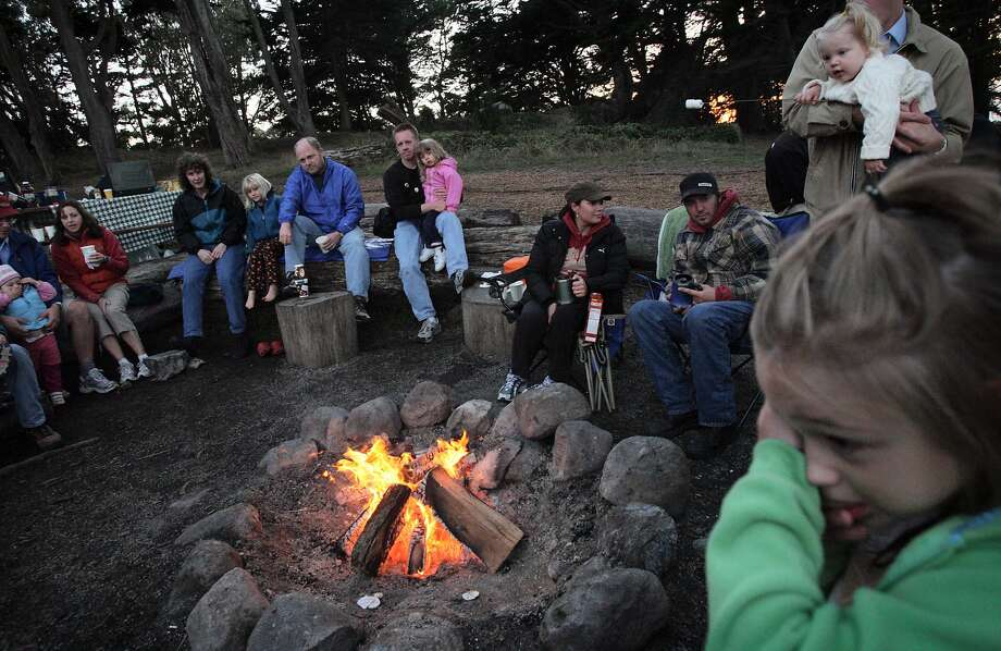 Zazie Huml, 6, (right) shields her eyes from the smoke during a family campfire program at Rob Hill Campground in the Presidio. The campfire, organized by the Crissy Field Center, offered families a chance to make S'mores, listen to stories from park rangers and sing campfire songs.  (Laura Morton/Special to the Chronicle) Photo: Laura Morton, Special To The Chronicle