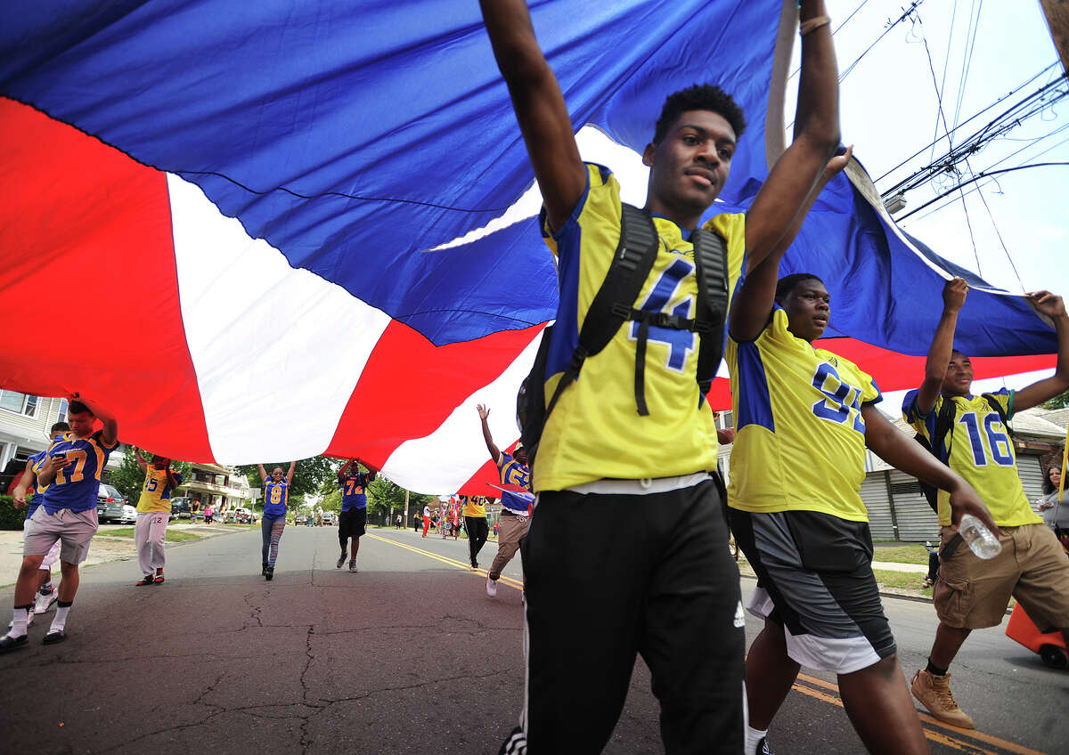 Harding High School football players march with an enormous Puerto Rican flag during the annual Puerto Rican Day Parade on North Avenue in Bridgeport, Conn. on Sunday, July 10, 2016.