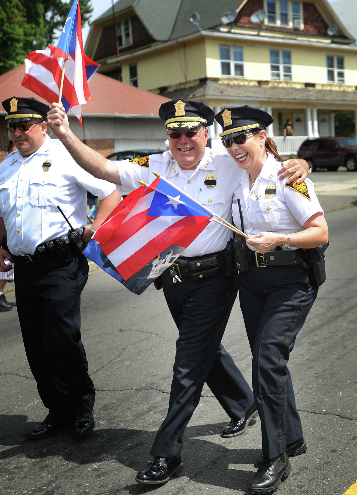 Bridgeport Police Chief A.J. Perez waves the Puerto Rican flag with Captain Rebecca Garcia as they march in the annual Puerto Rican Day Parade on North Avenue in Bridgeport, Conn. on Sunday, July 10, 2016.