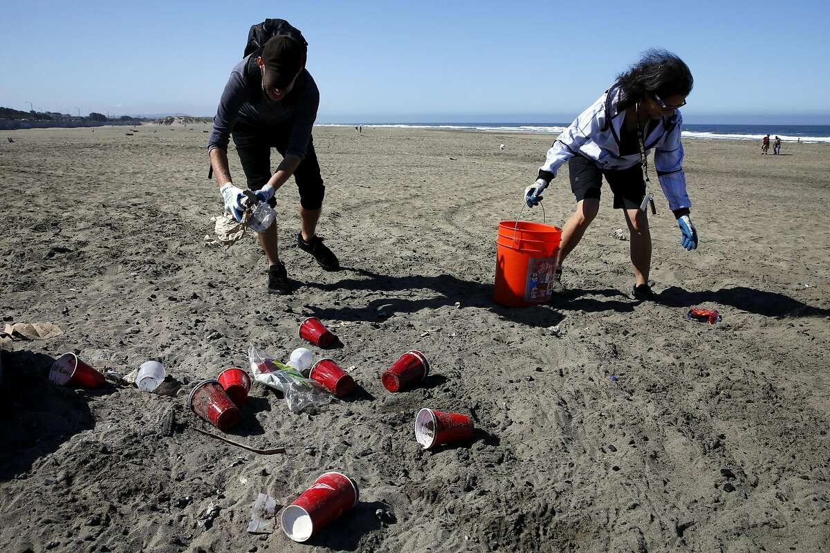 Chad Redden (left) and Joan Gerigk pick up trash during a volunteer event at Ocean Beach in San Francisco, California, on Sunday, July 10, 2016.