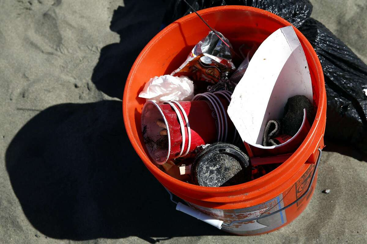 A plastic bin full of trash picked up from Ocean Beach.