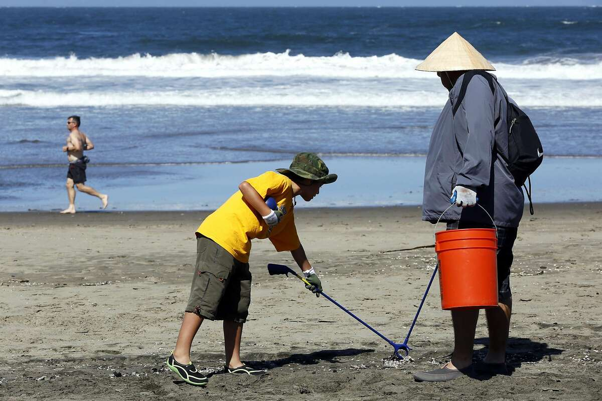 Paul Castor II (center) and Paul Castor pick up trash during a volunteer event at Ocean Beach in San Francisco, California, on Sunday, July 10, 2016.