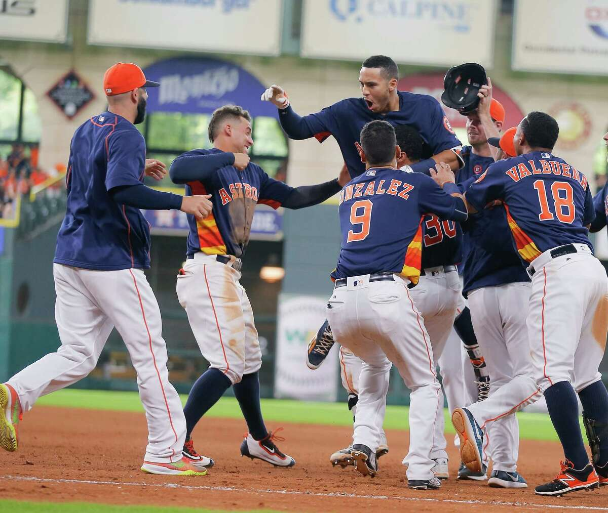 HOUSTON, TX - JULY 10: Carlos Correa #1 of the Houston Astros (C) is congratulated by his teammates after beating out an infield hit in the ninth inning allowing the winning run to beat the Oakland Athletics at Minute Maid Park on July 10, 2016 in Houston, Texas.