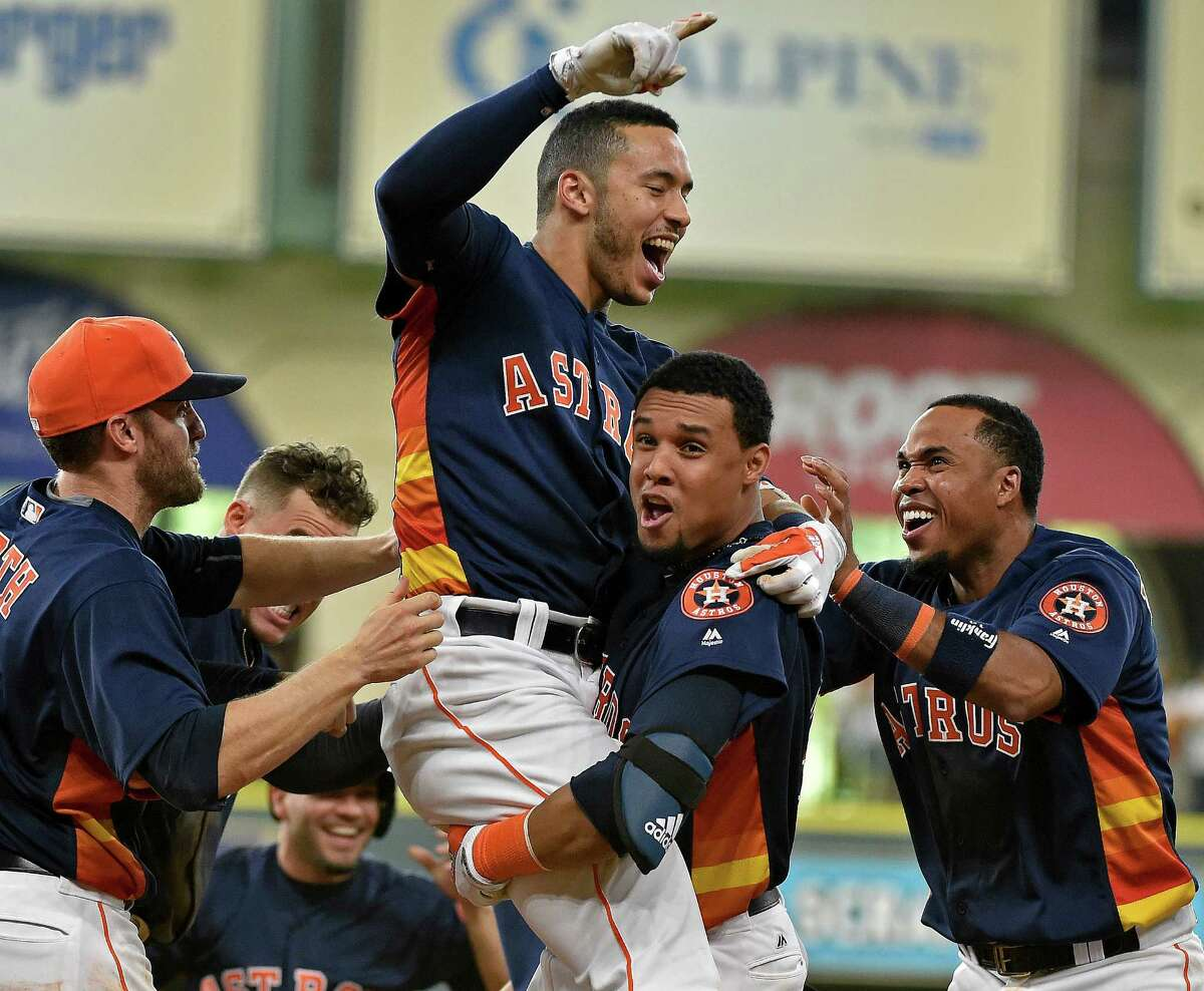 Houston Astros' Carlos Correa celebrates his game-winning RBI single with Carlos Gomez and teammates in the 10th inning of a baseball game against the Oakland Athletics, Sunday, July 10, 2016, in Houston. Houston won 2-1. (AP Photo/Eric Christian Smith)