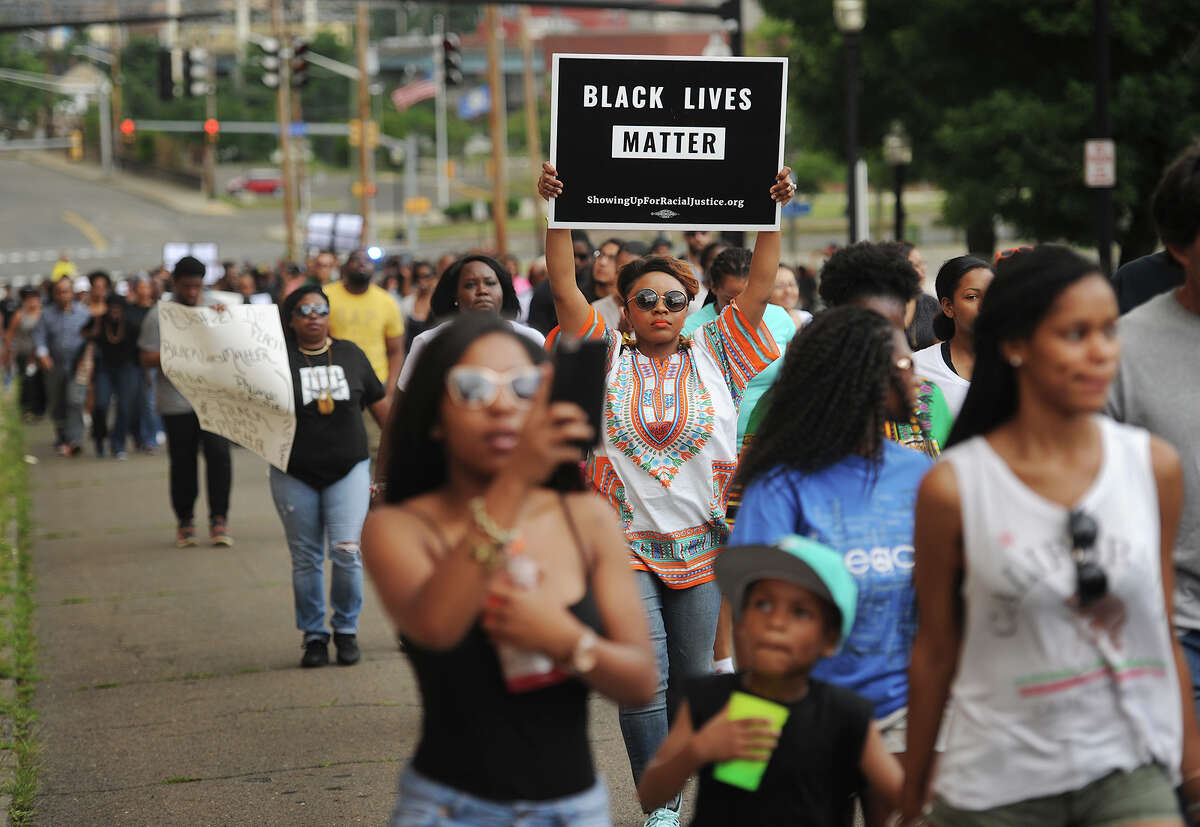 Bennyta Thompson, of Bridgeport, holds a Black Lives Matter sign aloft as she marches as one of several hundred up Congress Street in Bridgeport, Conn. on Sunday, July 10, 2016. Protesting last week's killing of black men by police officers in Louisiana and Minnesota, protesters marched from Mount Aery Baptist Church on Frank Street to Bridgeport Police Headquarters on Congress Street.