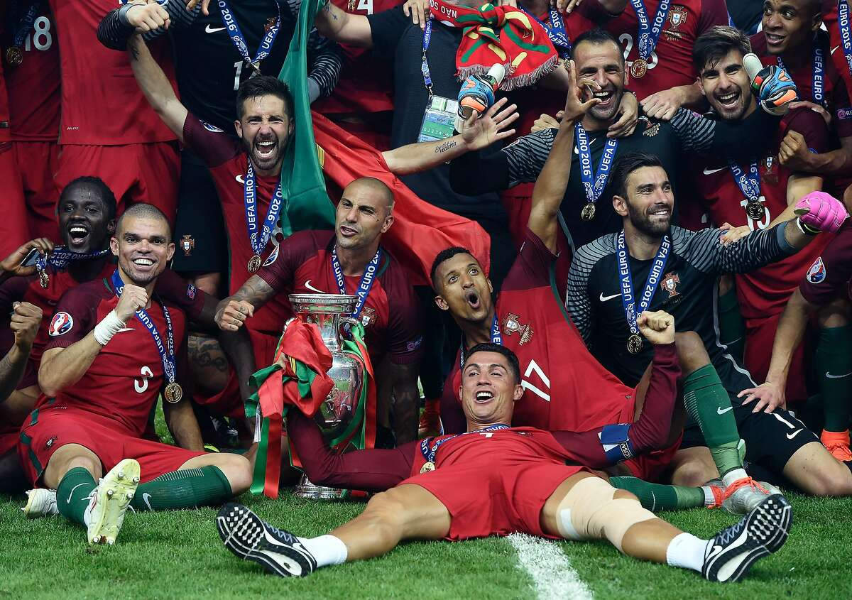 (From L) Portugal's forward Eder, Portugal's defender Pepe, Portugal's midfielder Joao Moutinho, Portugal's forward Ricardo Quaresma, Portugal's forward Nani, Portugal's forward Cristiano Ronaldo and Portugal's goalkeeper Rui Patricio pose with the trophy as they celebrate after beating France during the Euro 2016 final football match at the Stade de France in Saint-Denis, north of Paris, on July 10, 2016. / AFP PHOTO / PHILIPPE DESMAZESPHILIPPE DESMAZES/AFP/Getty Images
