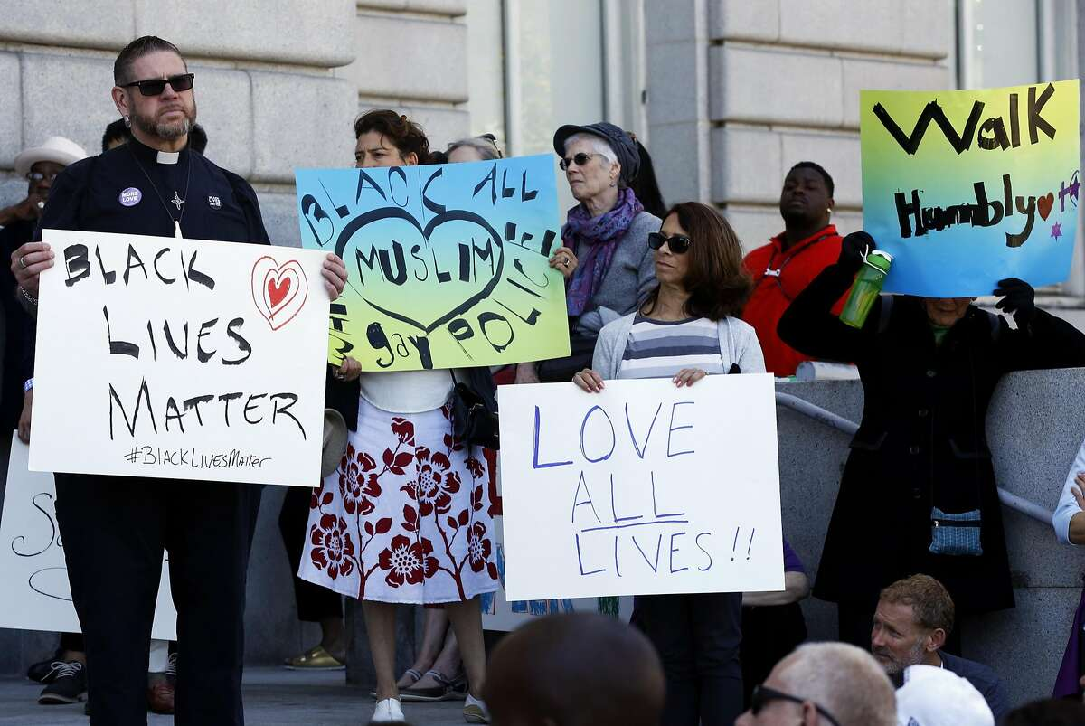 People hold signs during a rally at City Hall in San Francisco, California, on Sunday, July 10, 2016. Persons of faith gathered in response to the recent killings of two black men by police officers.