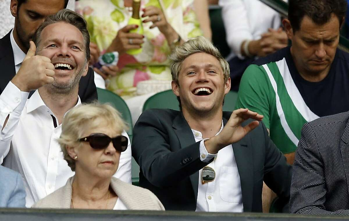 Niall Horan of One Direction, right, smiles watching the action during day eight of the Wimbledon Tennis Championships in London, Monday, July 4, 2016.