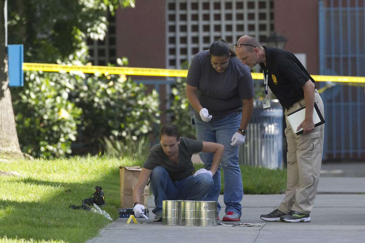 FILE - In this July 6, 2016, file photo, San Diego's Metro Arson Strike Team and SDPD homicide team gather evidence from the sidewalk and grassy area where a homeless person was attacked in downtown San Diego. A man injured during a series of attacks on homeless men in San Diego died at a hospital Sunday, July 10, police said. (John Gibbins/U-T San Diego via AP, File)