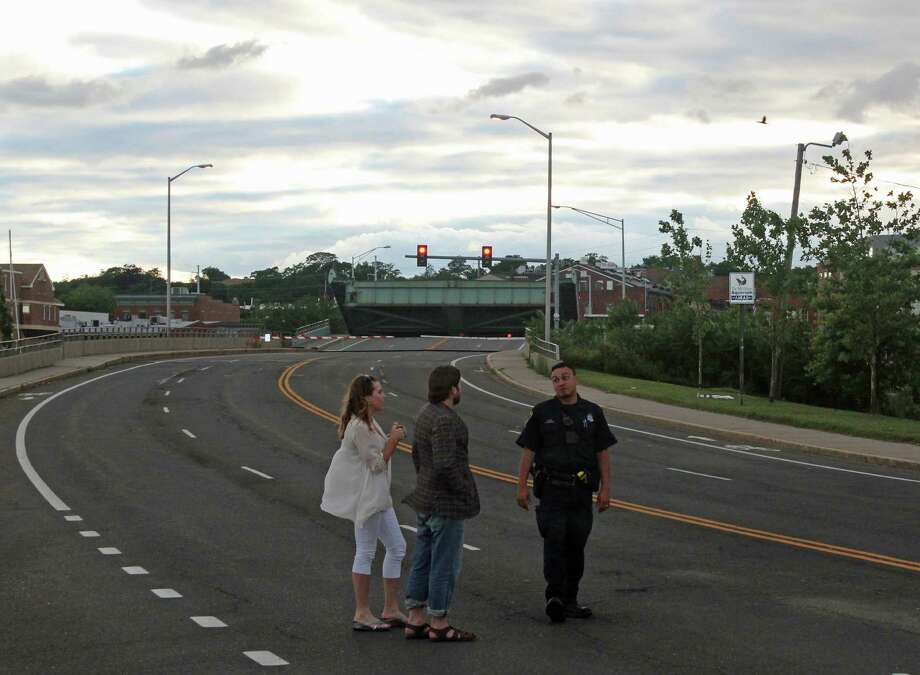 Pedestrians talk with a Norwalk police officer near the Stroffolino Bridge, which got stuck Sunday evening. Photo: Thane Grauel / Hearst Connecticut Media / Connecticut Post