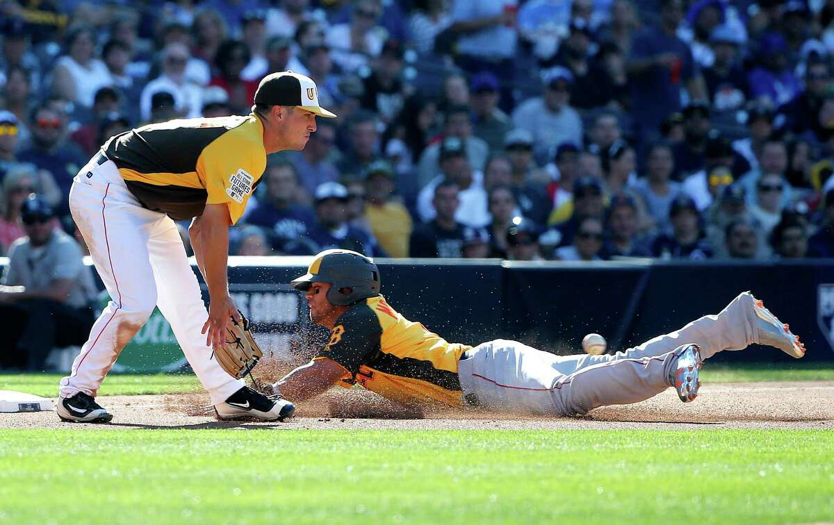 World Team's Yoan Moncada, right, of the Boston Red Sox, advances to third on a wild throw after stealing second as U.S. Team's Alex Bregman, of the Houston Astros waits for the throw during the third inning of the All-Star Futures baseball game, Sunday, July 10, 2016, in San Diego. (AP Photo/Lenny Ignelzi)