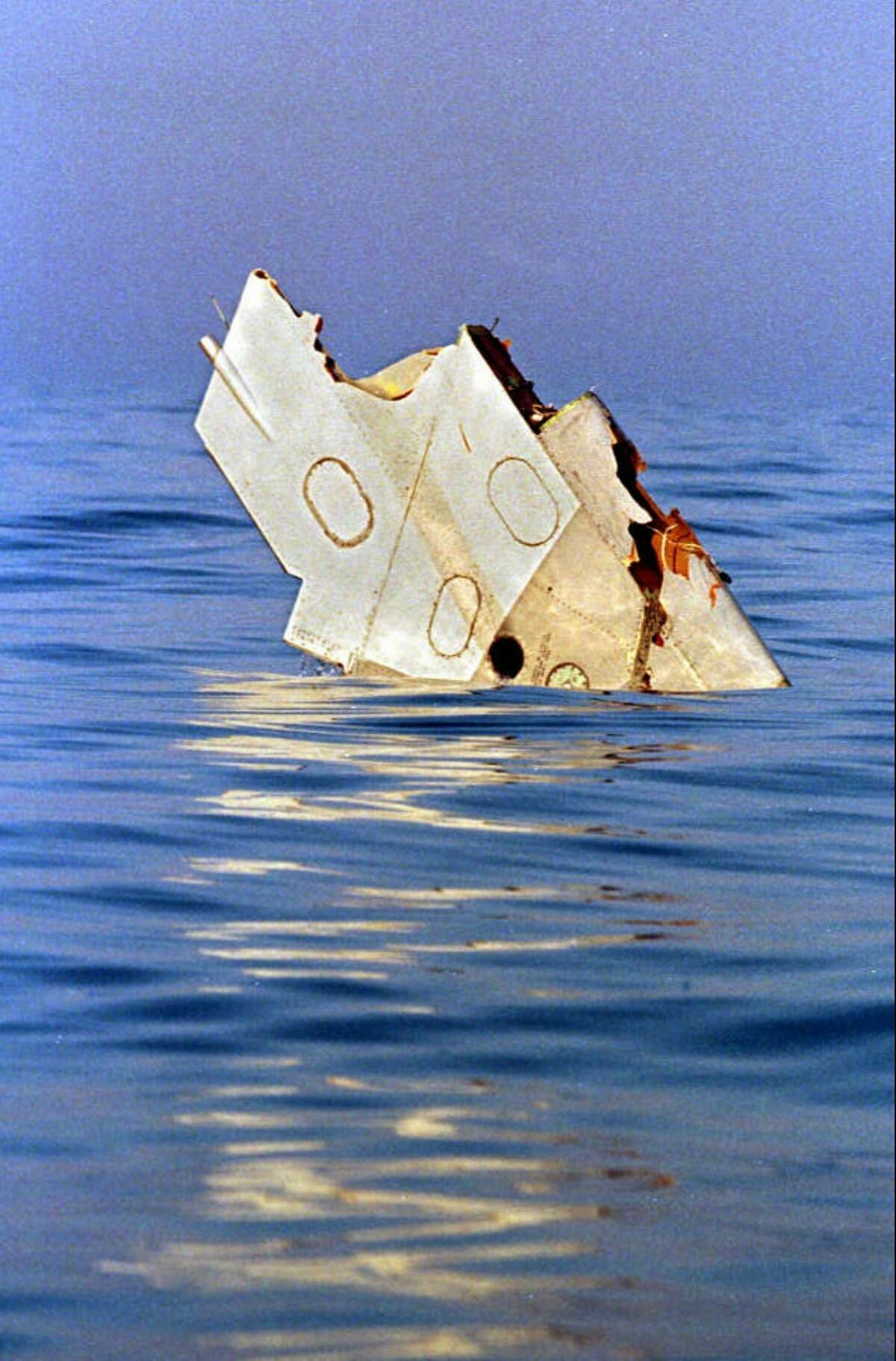 FILE - In this July 18, 1996, file photo, a piece of debris from TWA Flight 800 floats in the Atlantic Ocean off Long Island the day after the Boeing 747, carrying 230 people, exploded in a ball of fire, killing everyone on board. Twenty years later, some still debate National Transportation Safety Board findings that the aircraft was brought down by a center fuel-tank explosion ignited by a spark from a short circuit. (John Levy/ AFP via AP, Pool, File) ORG XMIT: NYR301