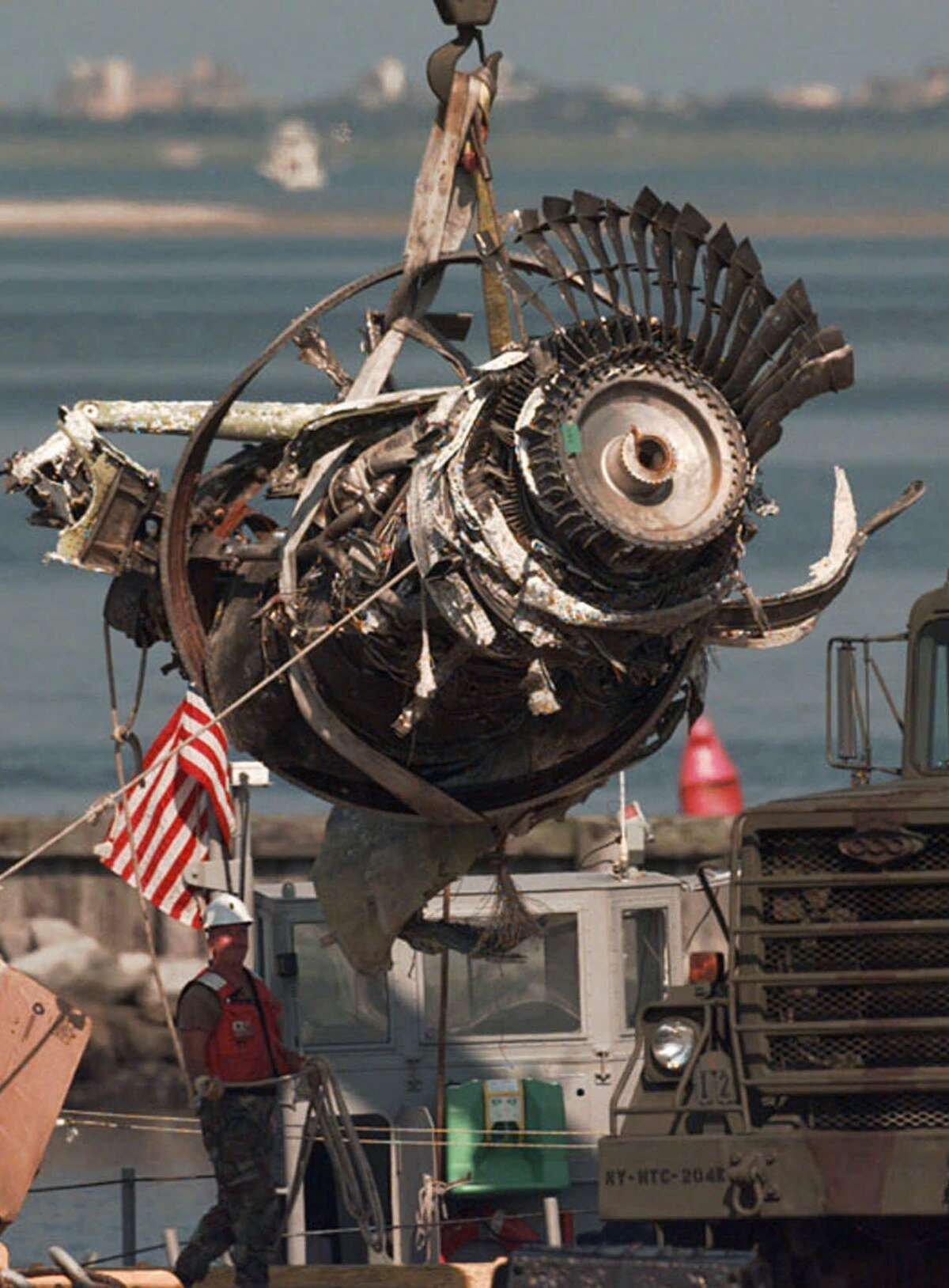 FILE - In this Aug. 15, 1996, file photo, the final engine to be salvaged from the wreckage of TWA Flight 800 is loaded by crane onto a truck at the U.S. Coast Guard Shinnecock Station in Hampton Bays, N.Y. Twenty years after the Boeing 747 carrying 230 people exploded in a ball of fire, killing everyone on board, some still debate National Transportation Safety Board findings that the aircraft was brought down by a center fuel-tank explosion ignited by a spark from a short circuit. (AP Photo/Mark Lennihan, File) ORG XMIT: NYR302