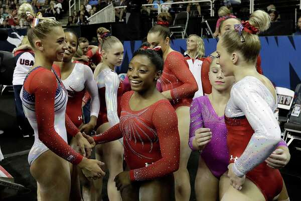 Simone Biles, center, smiles as she gathers with other competitors after the women's U.S. Olympic gymnastics trials in San Jose, Calif., Sunday, July 10, 2016. (AP Photo/Gregory Bull)