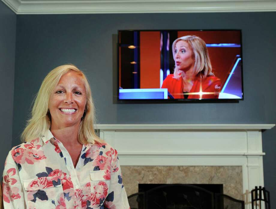 "Kristin Bivona stands by a television at her Stamford home as it shows a video of her recent appearance as a contestant on the game show ""The $100,000 Pyramid"" on Thursday. Photo: Bob Luckey Jr. / Hearst Connecticut Media / Greenwich Time"