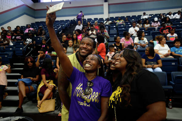 Fans take a photo with Jonathan Babineaux during the Babineaux Family Foundation's Celebrity All-Star Classic basketball game on Saturday.  Photo taken Saturday 7/9/16 Ryan Pelham/The Enterprise