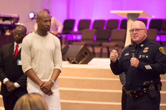 Pastor Keion Henderson listens to Capt. Greg Fremin at his service at The Lighthouse church.
