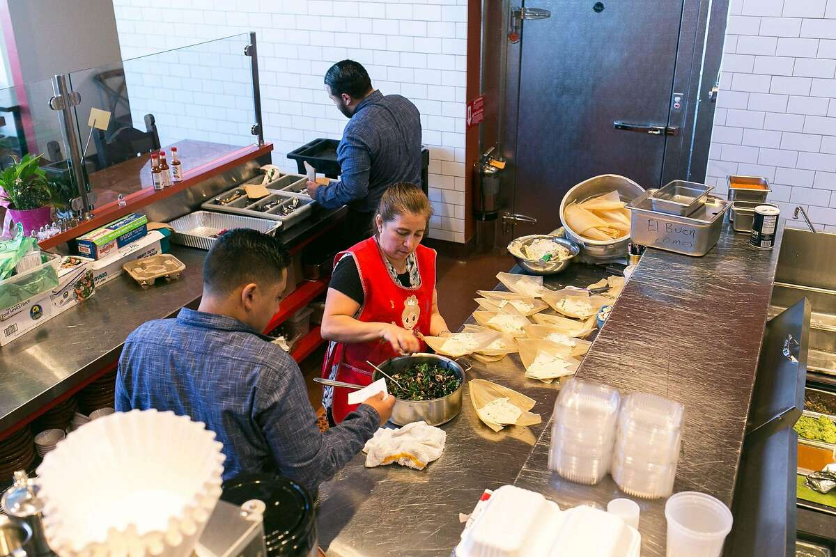 Isabel Caudillo makes tamales while her sons, Vladamir (left) and Hansel Caudillo serve customers at El Buen Comer in S.F.