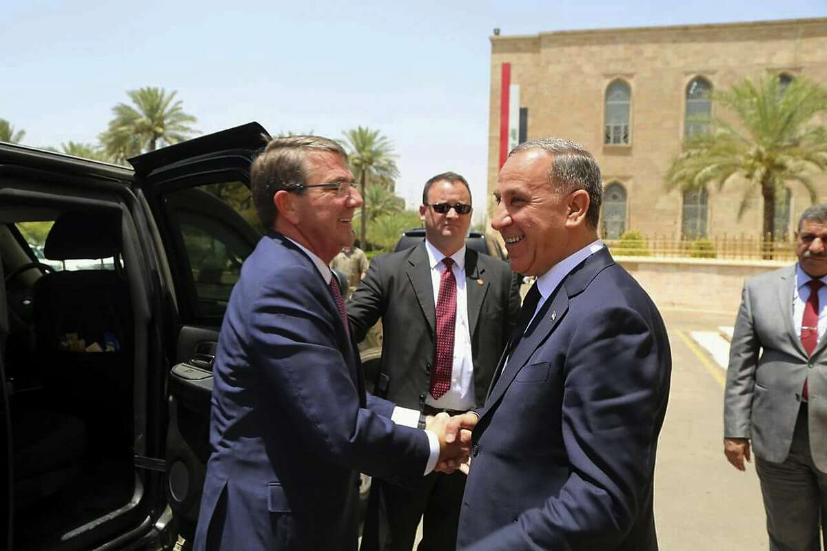 Visiting U.S. Defense Secretary Ash Carter, left, shakes hands with Iraqi Defense Minister Khaled al-Obeidi at the Ministry of Defense, Baghdad, Iraq, Monday, July 11, 2016. As Carter arrived in Iraq, Monday, he said U.S. and coalition forces will use the newly retaken air base in Qayara as a staging hub as Iraqi security forces move closer to the long-awaited battle to recapture Mosul from Islamic State militants. Carter landed in Baghdad on an unannounced visit and says U.S. advisers are prepared to accompany Iraqi battalions, if needed, as those units move closer to the fight for Mosul. (AP Photo)