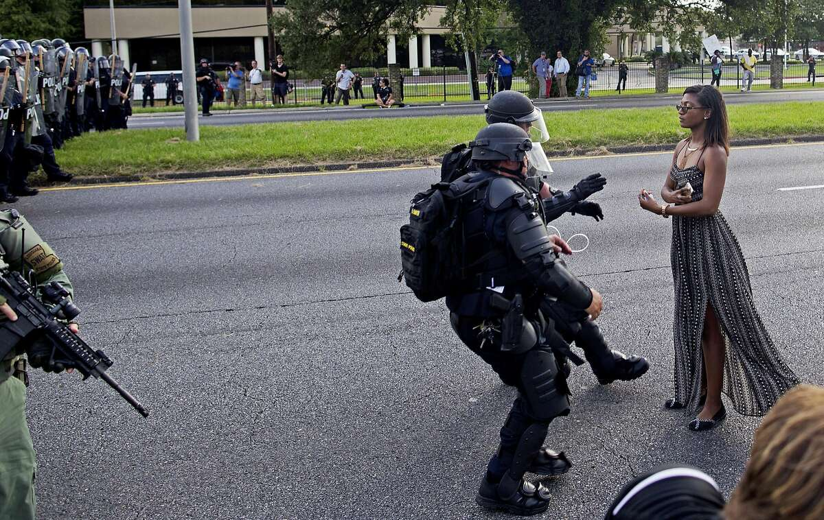 FILE In this Saturday, July 9, 2016 file photo, A protester is grabbed by police officers in riot gear after she refused to leave the motor way in front of the the Baton Rouge Police Department Headquarters in Baton Rouge, La. Police made nearly 200 arrests in Louisiana's capital city during weekend protests around the country in which people angry over police killings of young black men sought to block some major interstates. (AP Photo/Max Becherer)