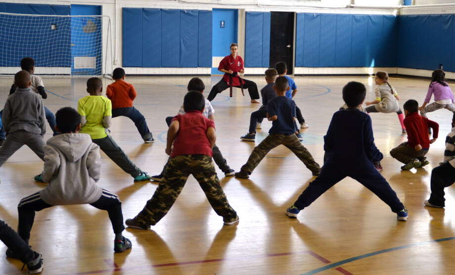 """Joshu Rebecca Siegal teaches a """"horse stance"""" to first graders during an event run by Kids Helping Kids in conjunction with The Dojo of Stamford at the Yerwood Center in Stamford, Conn. on Friday, Feb. 12, 2016. Photo: Contributed / Contributed Photo / Stamford Advocate  contributed"""