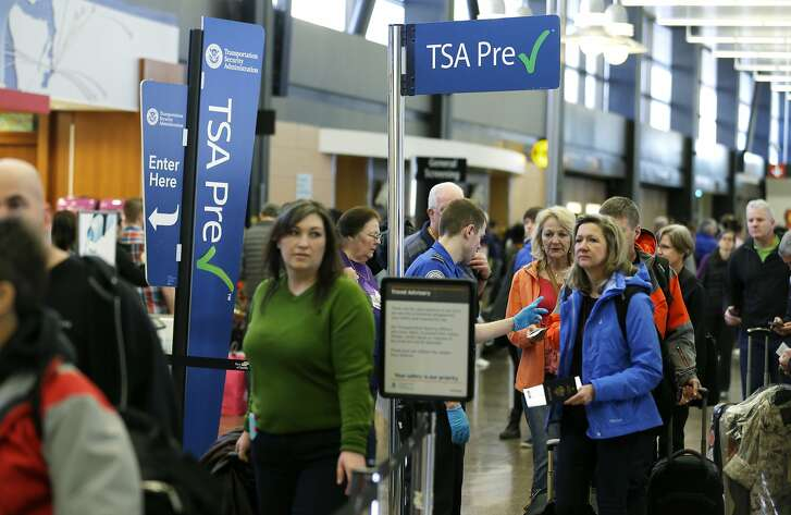 FILE - In this March 17, 2016, file photo, travelers authorized to use the Transportation Security Administration's PreCheck expedited security line at Seattle-Tacoma International Airport in Seattle have their documents checked by TSA workers. Thousands of fliers enrolled in trusted traveler programs such as PreCheck aren�t getting the expedited screening they paid for because of clerical errors with their reservations. (AP Photo/Ted S. Warren, File)