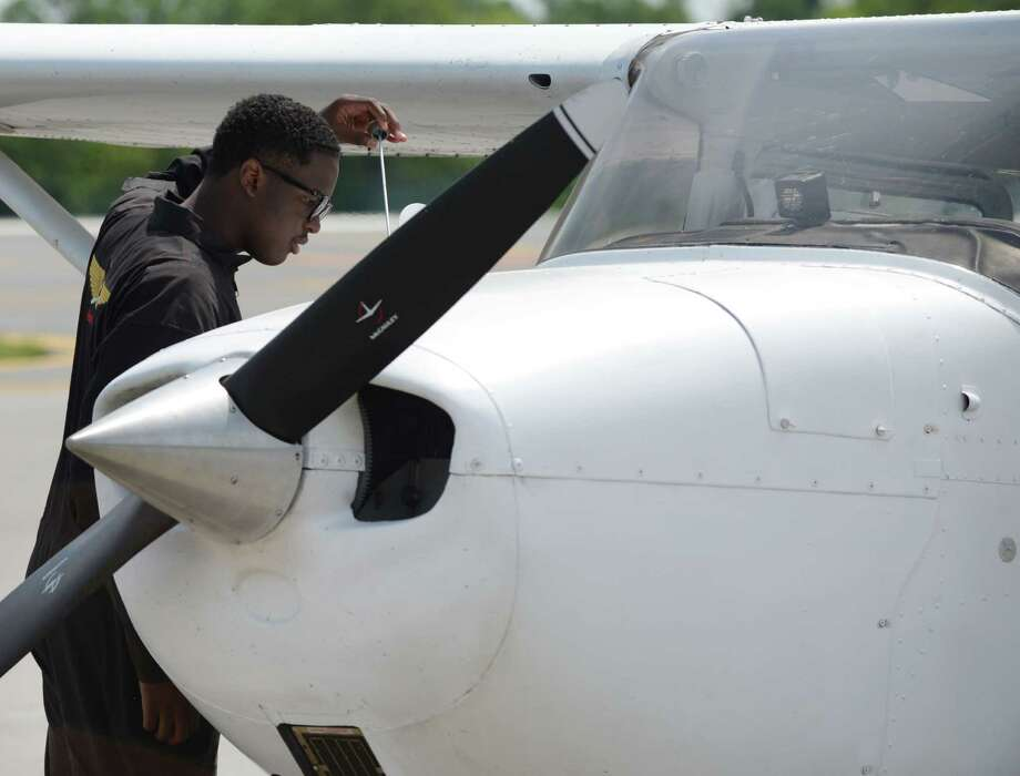 Isaiah Cooper, 16, of Compton, Calif., conducts a post-flight inspection after landing at Albany International Airport on Monday, July 11, 2016, in Colonie, N.Y. Cooper is attempting to become the youngest African-American pilot to fly around the continental U.S. He has a goal of being youngest pilot to fly solo around Earth. (Will Waldron/Times Union) Photo: Will Waldron / 20037286A