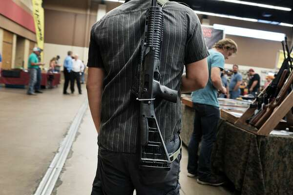 FORT WORTH, TX - JULY 10:  A man walks around a gun show with his gun on July 10, 2016 in Fort Worth, Texas. The Dallas and Forth Worth areas are still mourning the deaths of five police officers last Thursday evening by a lone gunman.  (Photo by Spencer Platt/Getty Images)
